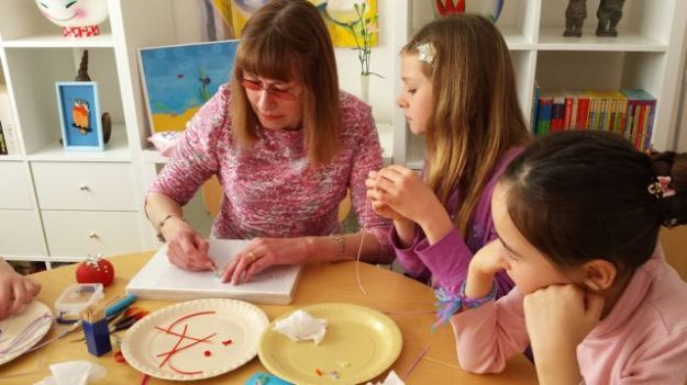 Celia and her friend Lucy (centre) look on as I show them how to create an eccentric coil.